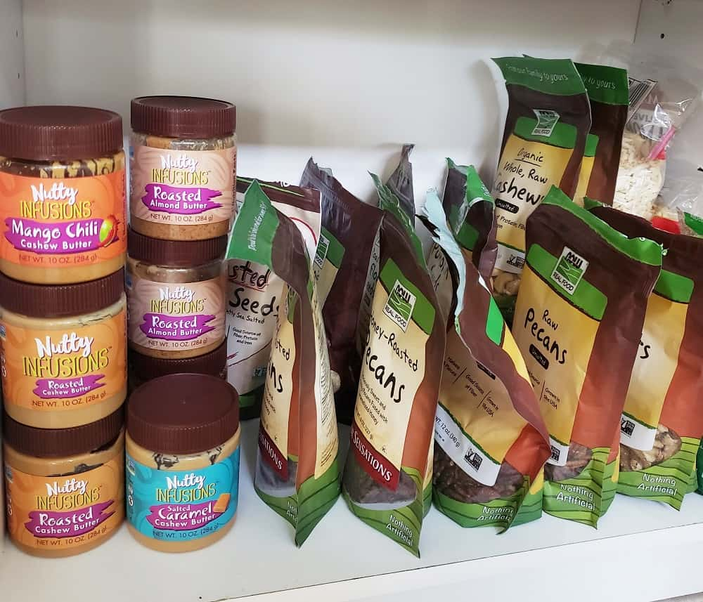 a shelf in a pantry with lots of different nuts and nut butters