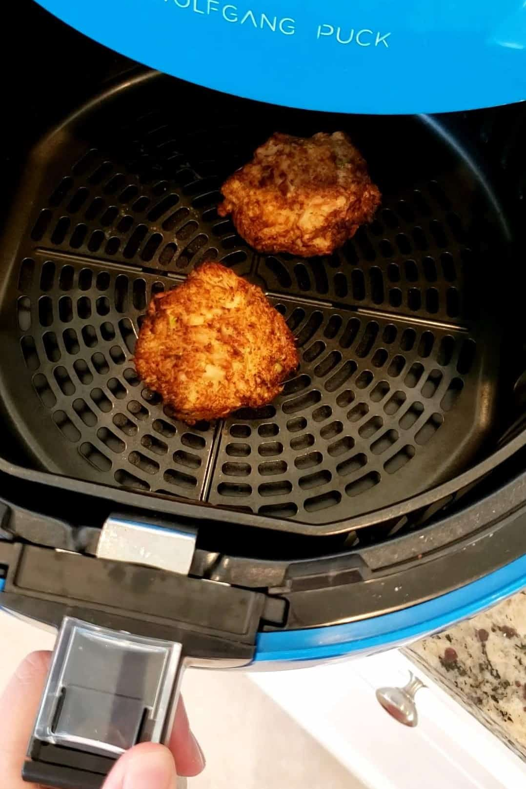two salmon patties in an air fryer basket after just finishing cooking