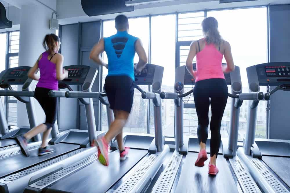 three treadmills with people running on them