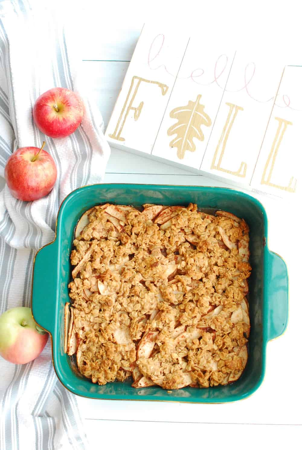 a baking dish full of honey apple crisp, next to a few apples and a flal