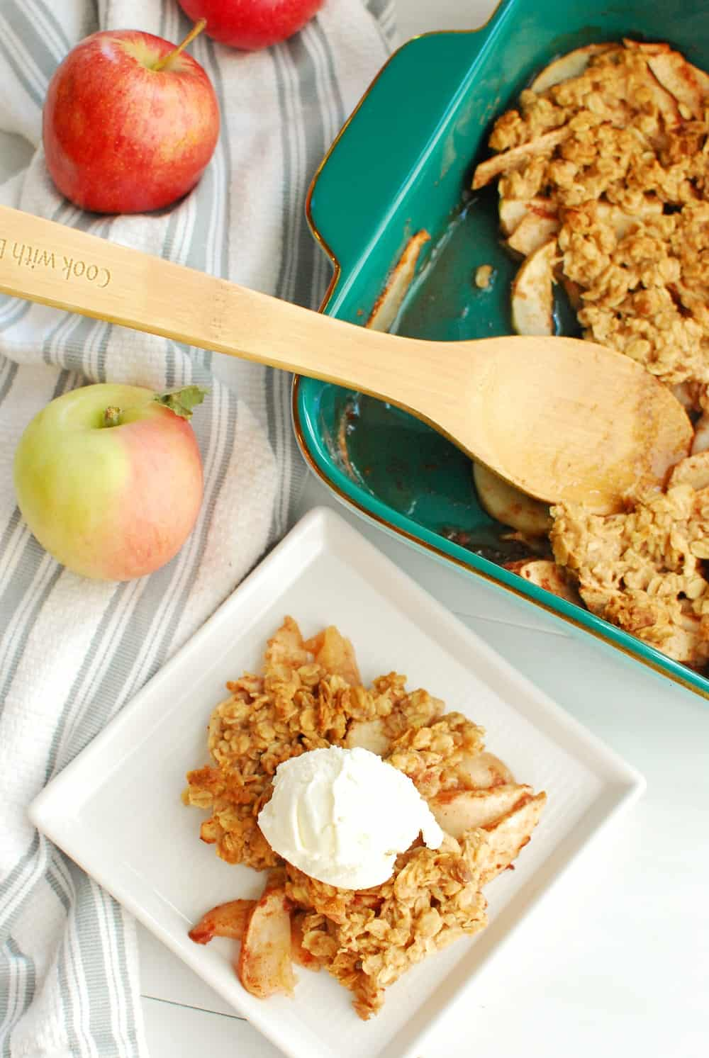 a scoop of honey apple crisp on a white plate with a scoop of ice cream, next to a baking dish of apple crisp