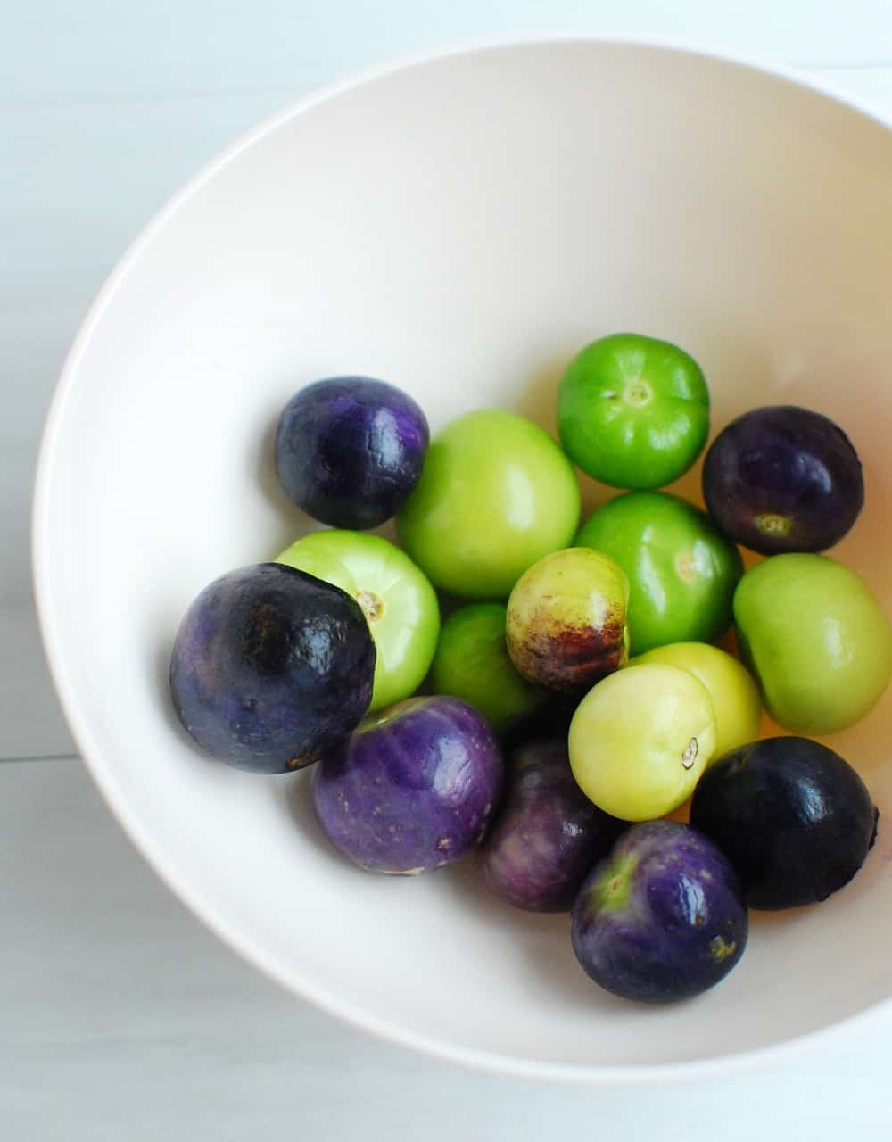 a bowl of green and purple tomatillos