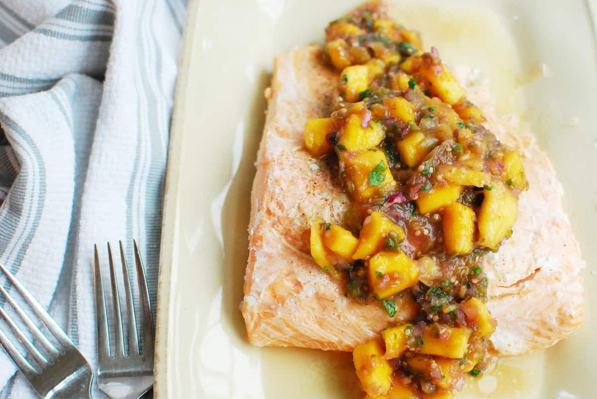 baked salmon topped with mango tomatillo salsa on a plate