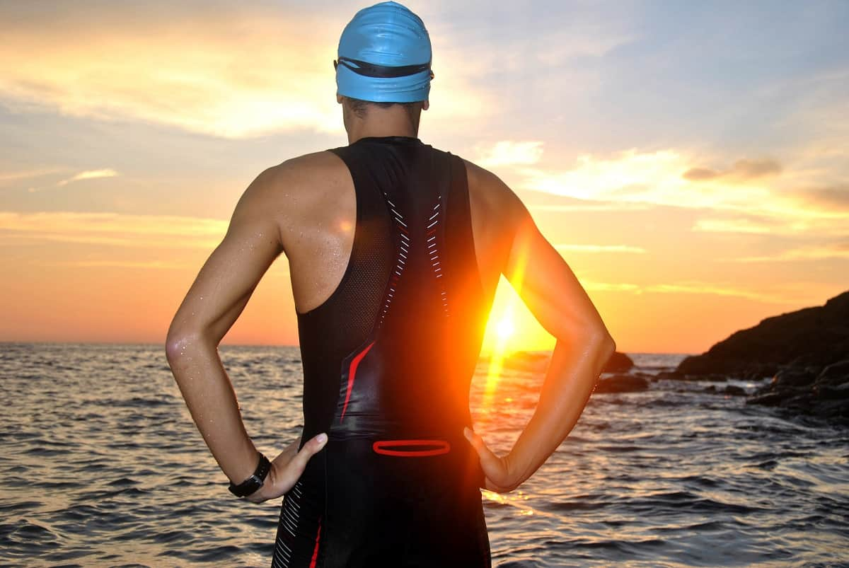 a triathlete facing the sea at sunrise, thinking about gifts they would love to receive