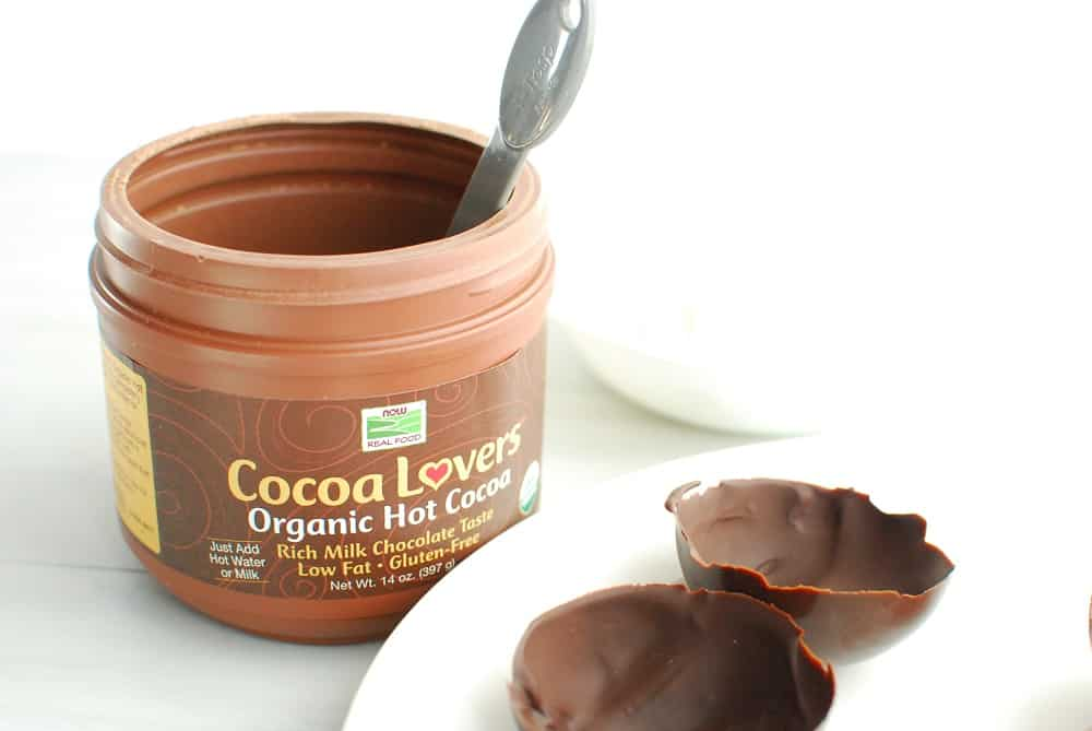 a container of hot chocolate mix with a measuring spoon next to two chocolate domes