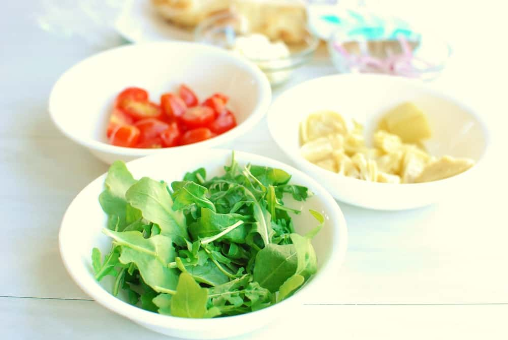 three small bowls, one with arugula, one with tomatoes, and one with artichokes