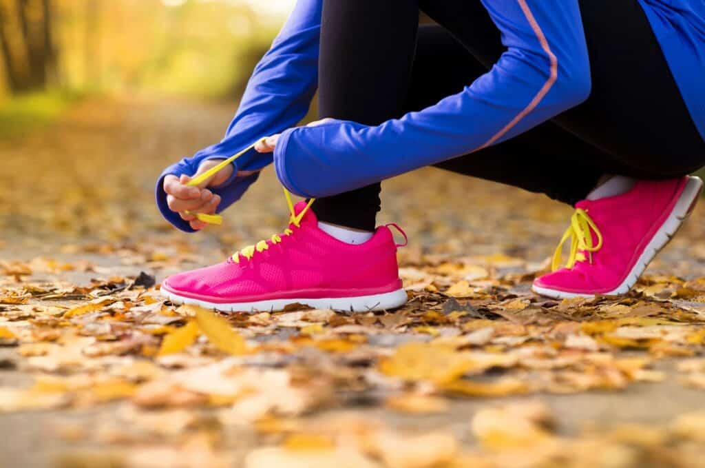 a woman tying her shoelaces getting ready to run a virtual turkey trot