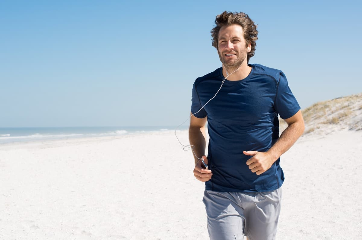 a male jogger who is running on the beach