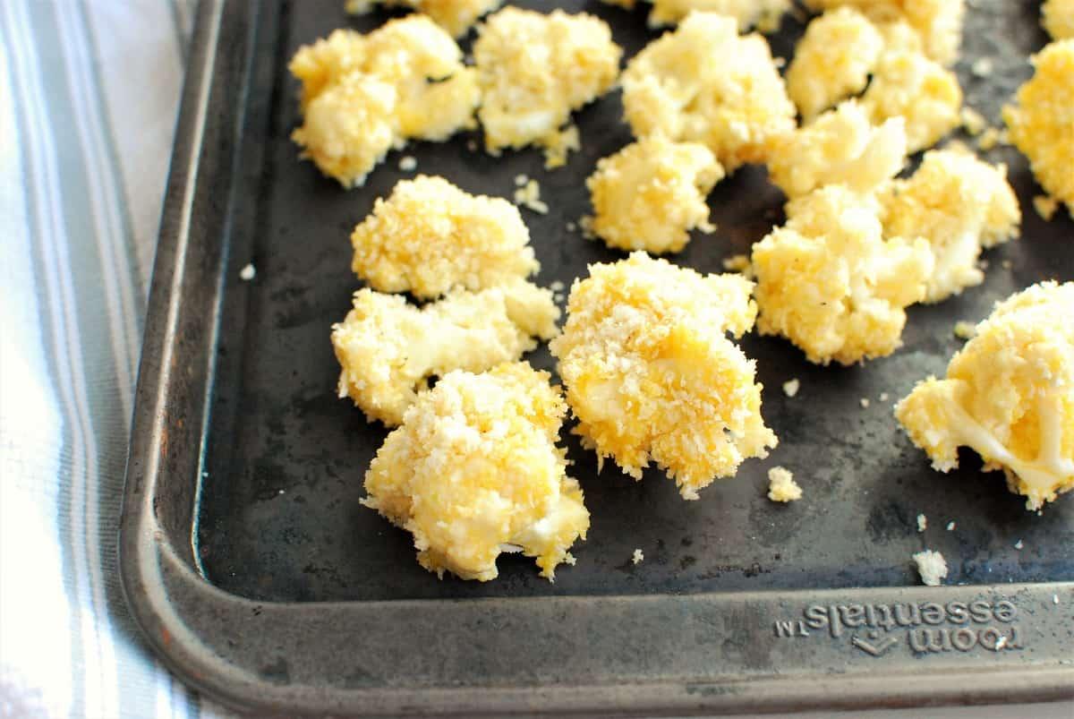 cauliflower coated in breadcrumbs on a baking sheet