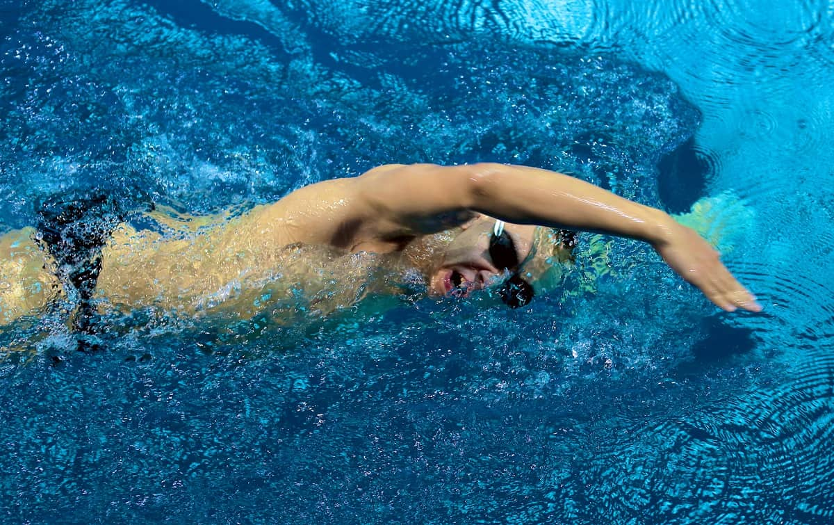 a male swimmer taking a breath during a freestyle stroke