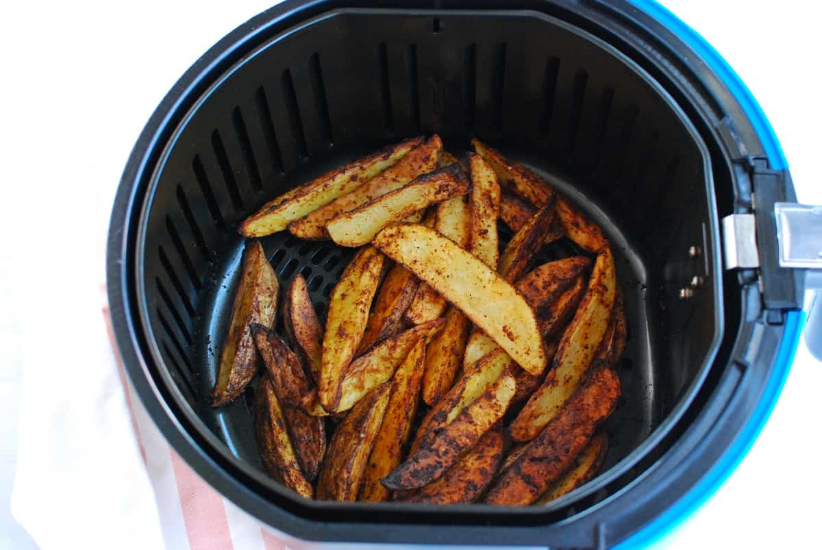 Potato wedges after just being cooked in the air fryer basket.