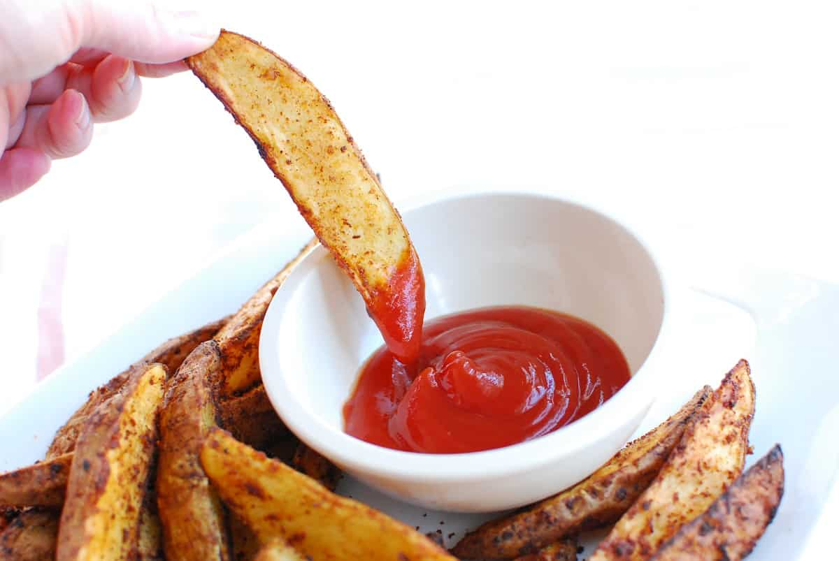 A woman's hand holding a potato wedge and dipping it in ketchup.