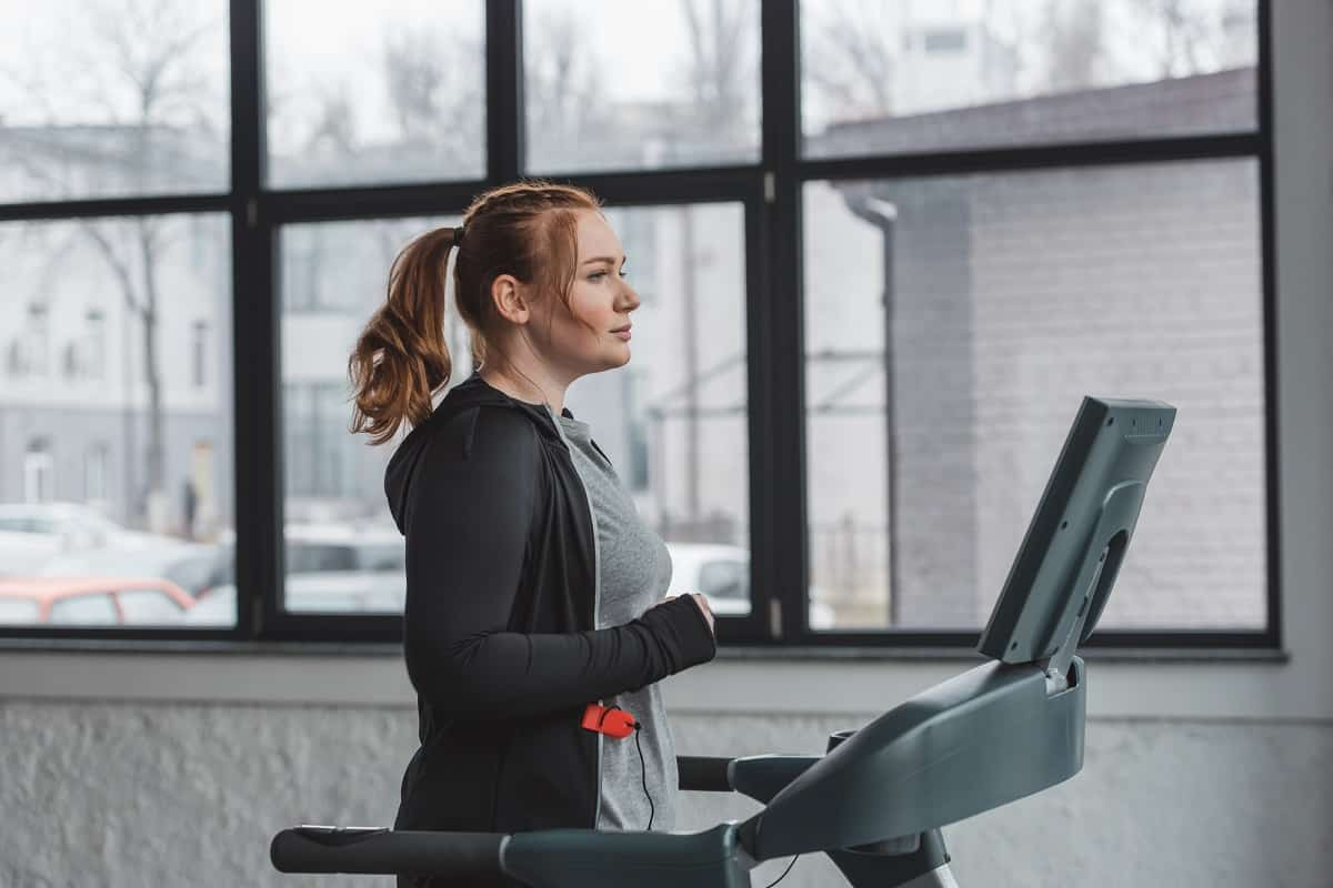 a woman walking on the treadmill doing a beginner workout