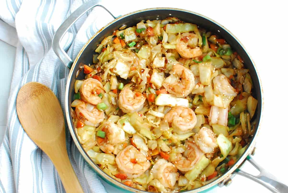 A sauté pan filled with shrimp egg roll in a bowl next to a wooden spoon.