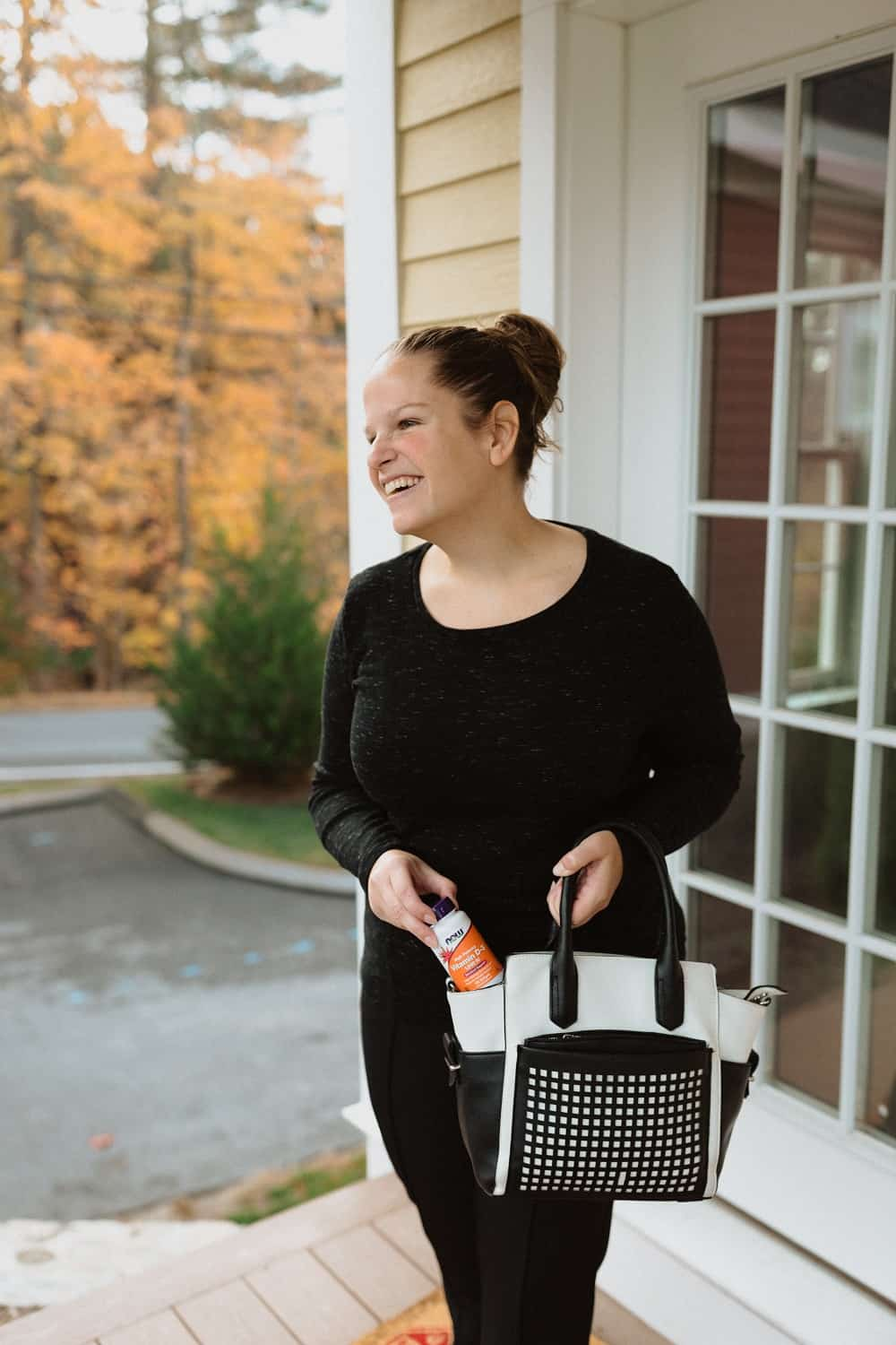 a woman taking a bottle of Vitamin D out of her purse