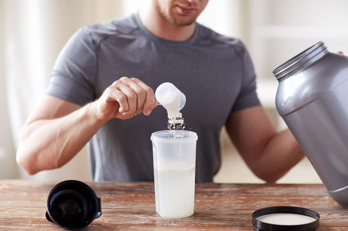 a man putting whey protein powder into a shaker bottle