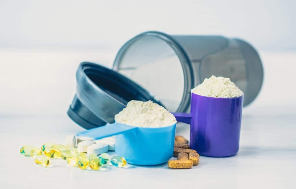 a scoop of whey protein powder and a scoop of collagen protein powder next to a shaker bottle