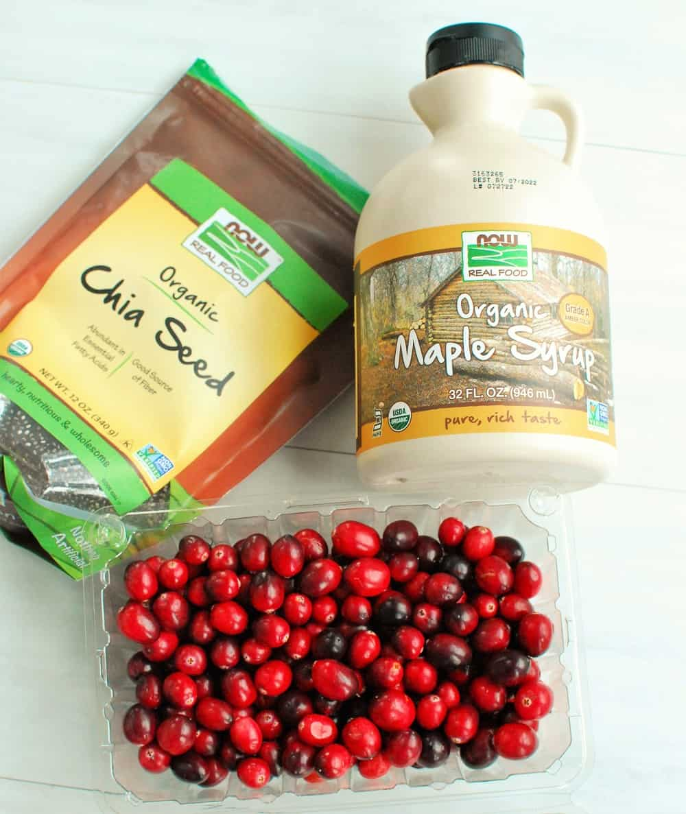 Fresh cranberries, a bag of chia seeds, and a jug of maple syrup.