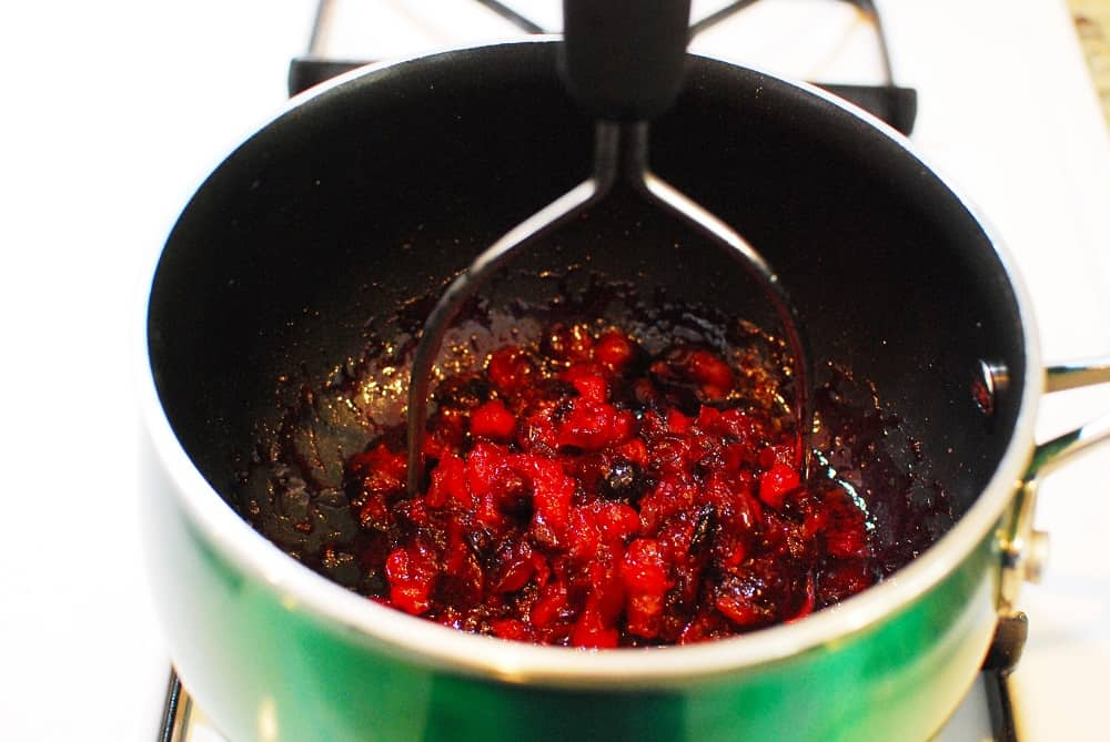 Mashing the cranberries in the pot with a potato masher.