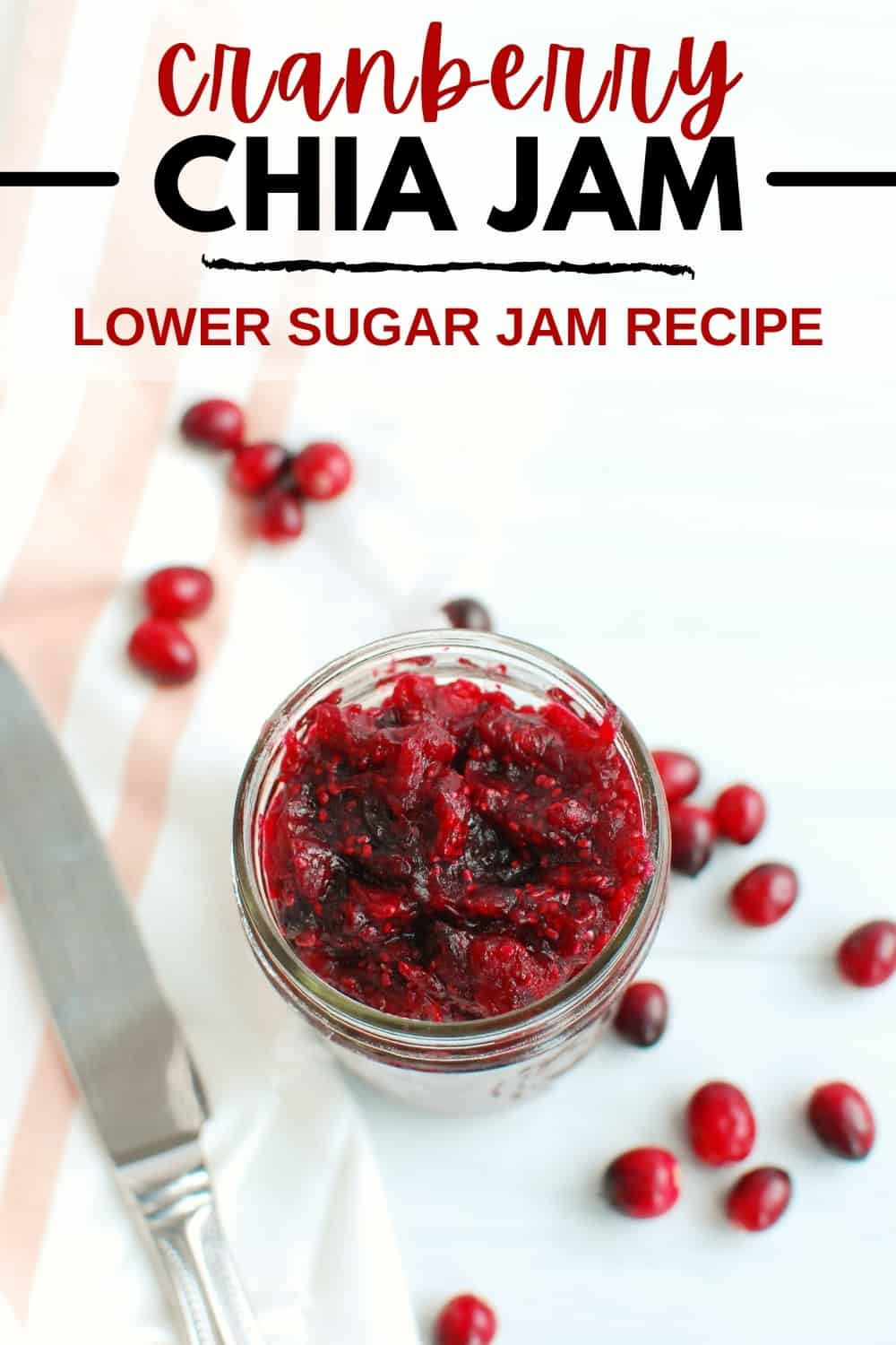 A jar of cranberry chia jam next to a butter knife with some fresh cranberries scattered around.