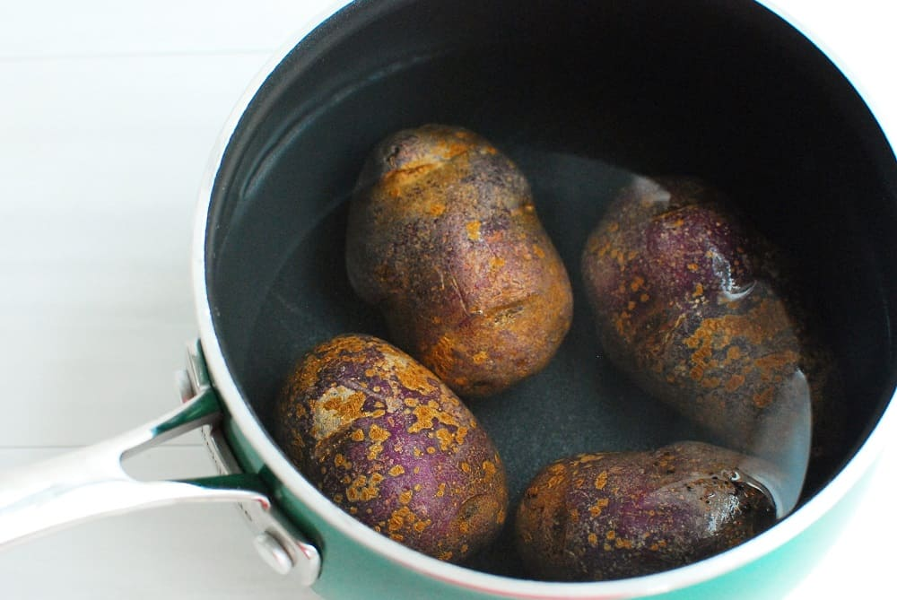 Purple potatoes in a pot of water.