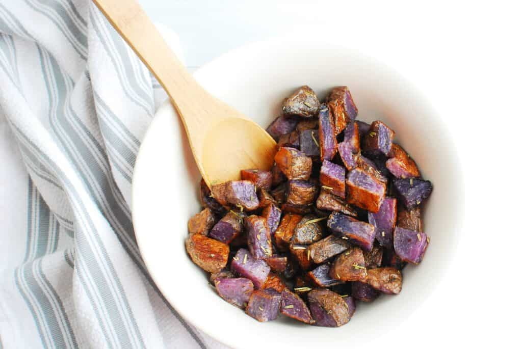 A bowl of herb roasted purple potatoes with a wooden spoon.