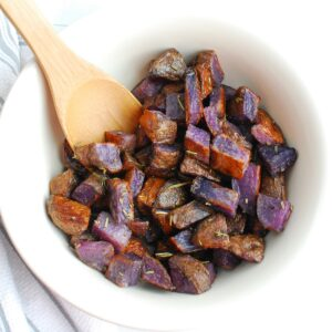 Herb roasted purple potatoes in a large serving bowl.