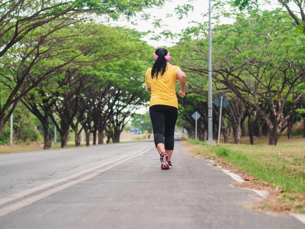 A beginner runner on the road learning how to run a mile without stopping.