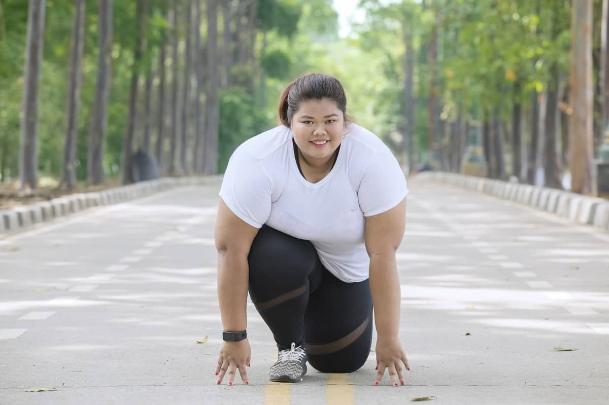 A woman kneeling on the ground getting ready to run.