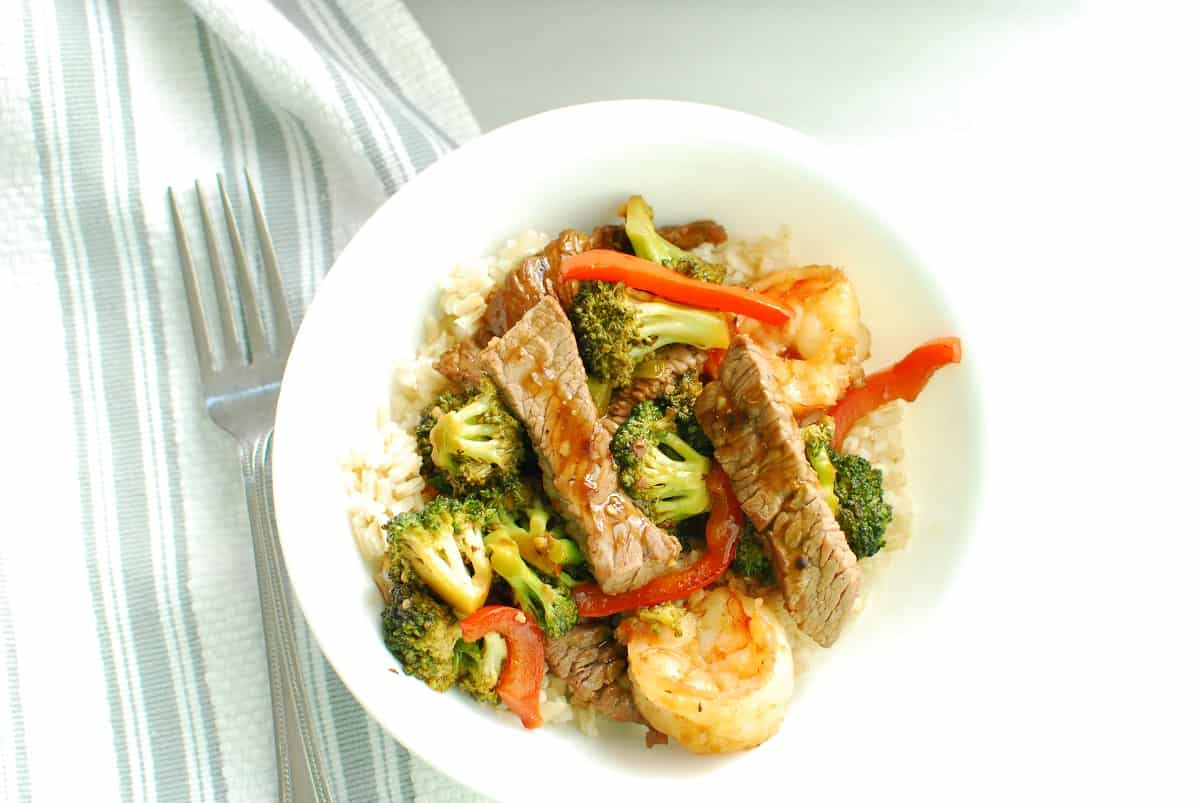 A bowl of steak and shrimp stir fry served over rice.