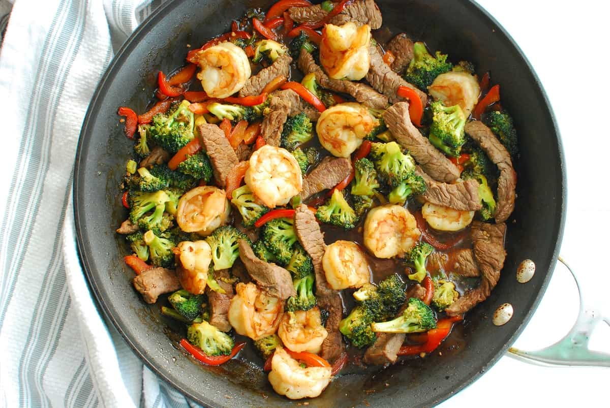 A skillet of shrimp and steak stir fry next to a striped napkin.