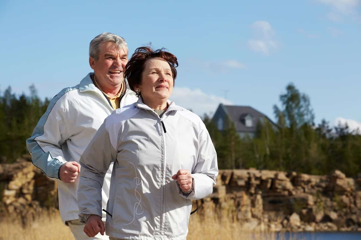 An older male and female running training together outside.