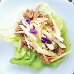 A hoisin turkey lettuce wrap on a white plate.