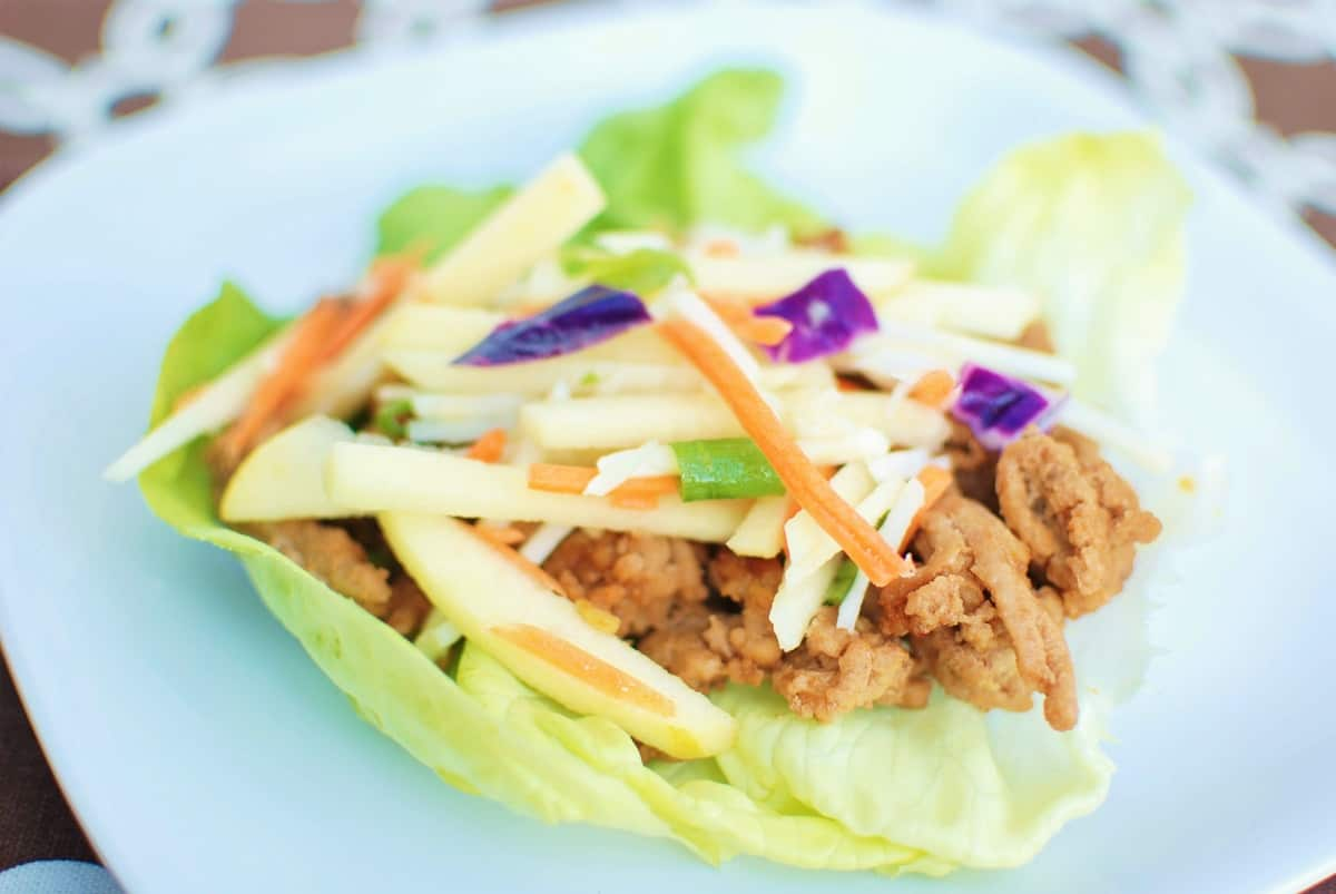 A hoisin ground turkey lettuce wrap on a white plate on top of a brown napkin.