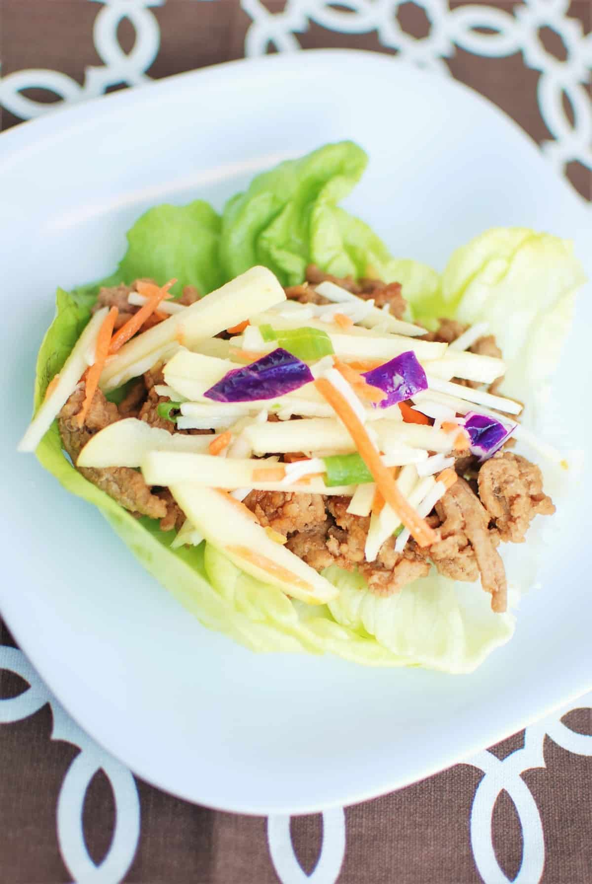 A lettuce wrap filled with hoisin ground turkey and cabbage apple slaw, on a plate, next to a brown napkin.
