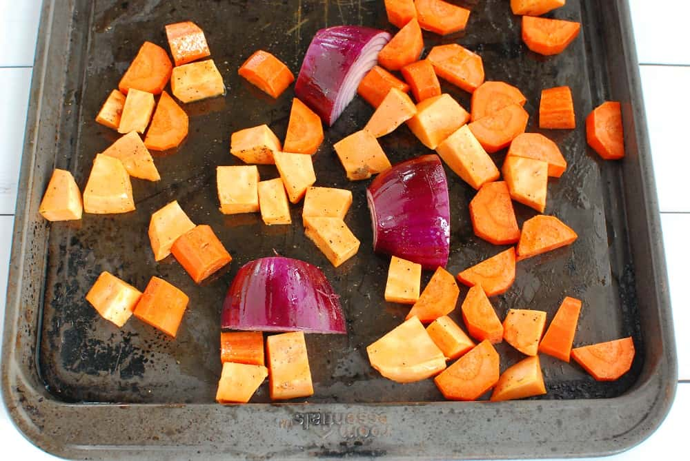 A baking sheet with chopped carrots and sweet potatoes, and a quartered red onion.
