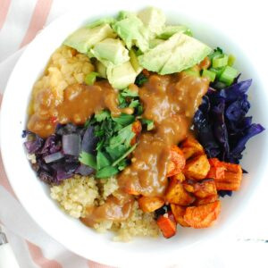 A quinoa lentil bowl with veggies topped with peanut sauce, next to a white and pink napkin.