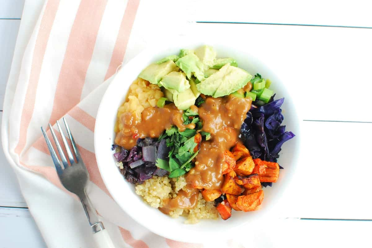 A lentil quinoa bowl with lots of veggies and peanut sauce on top.