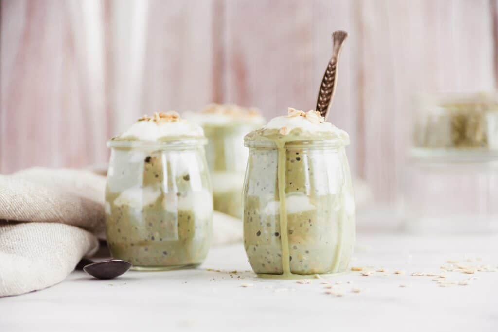 Several jars of matcha overnight oats, one of which has a spoon in it.