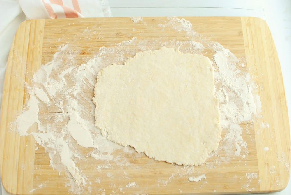 Pizza dough that's been rolled out flat on a wooden board.