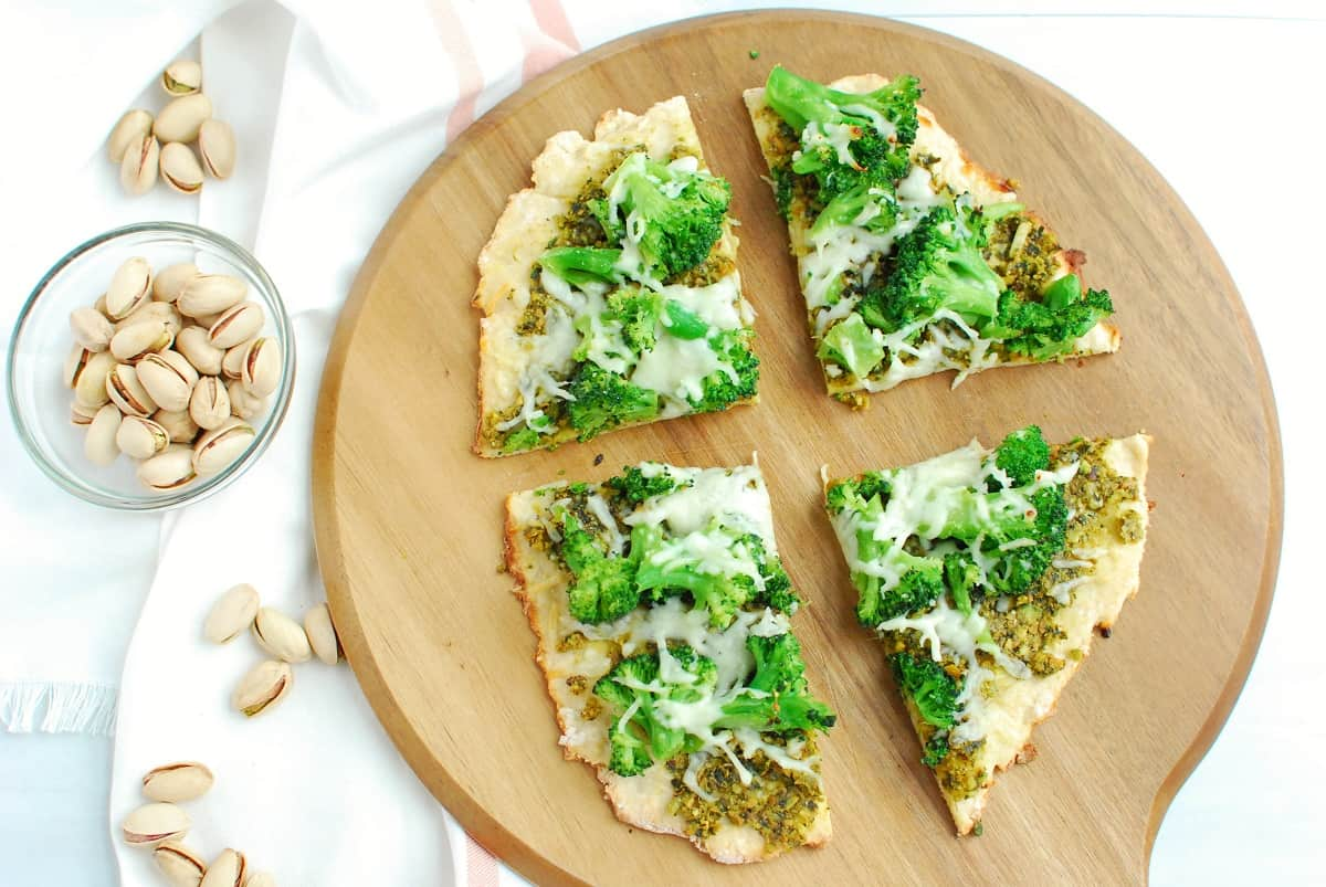 Four slices of pistachio pesto pizza on a cutting board, next to some scattared in-shell pistachios.