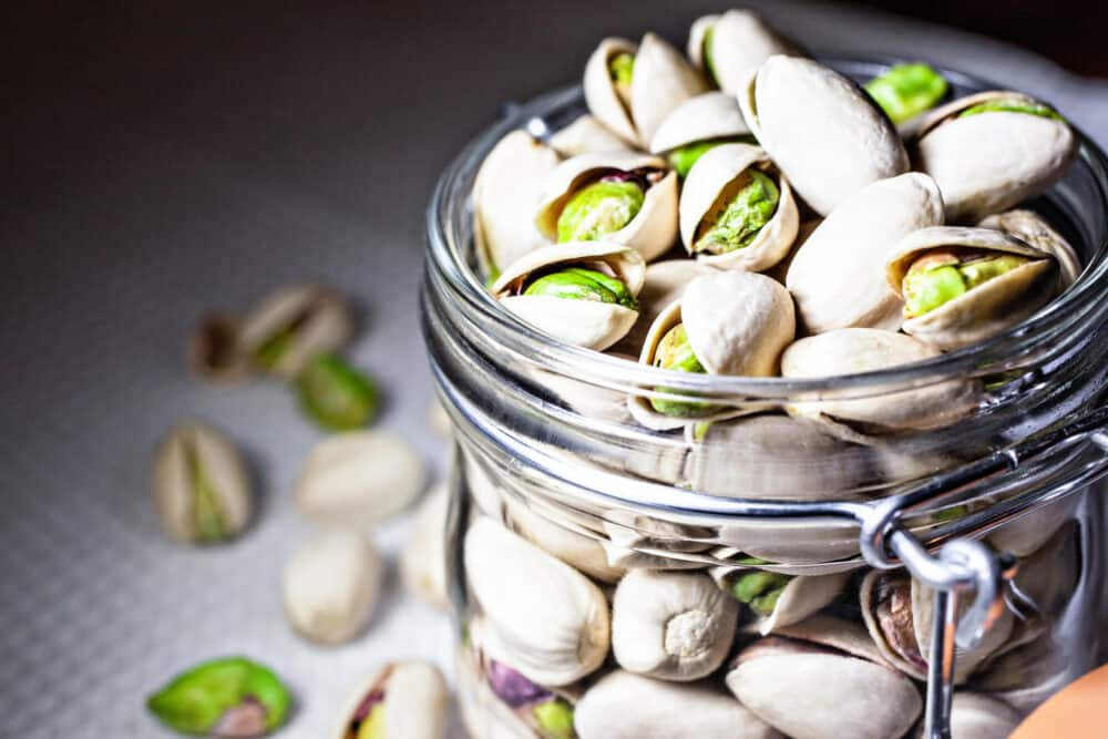 Pistachios in a clear glass jar.
