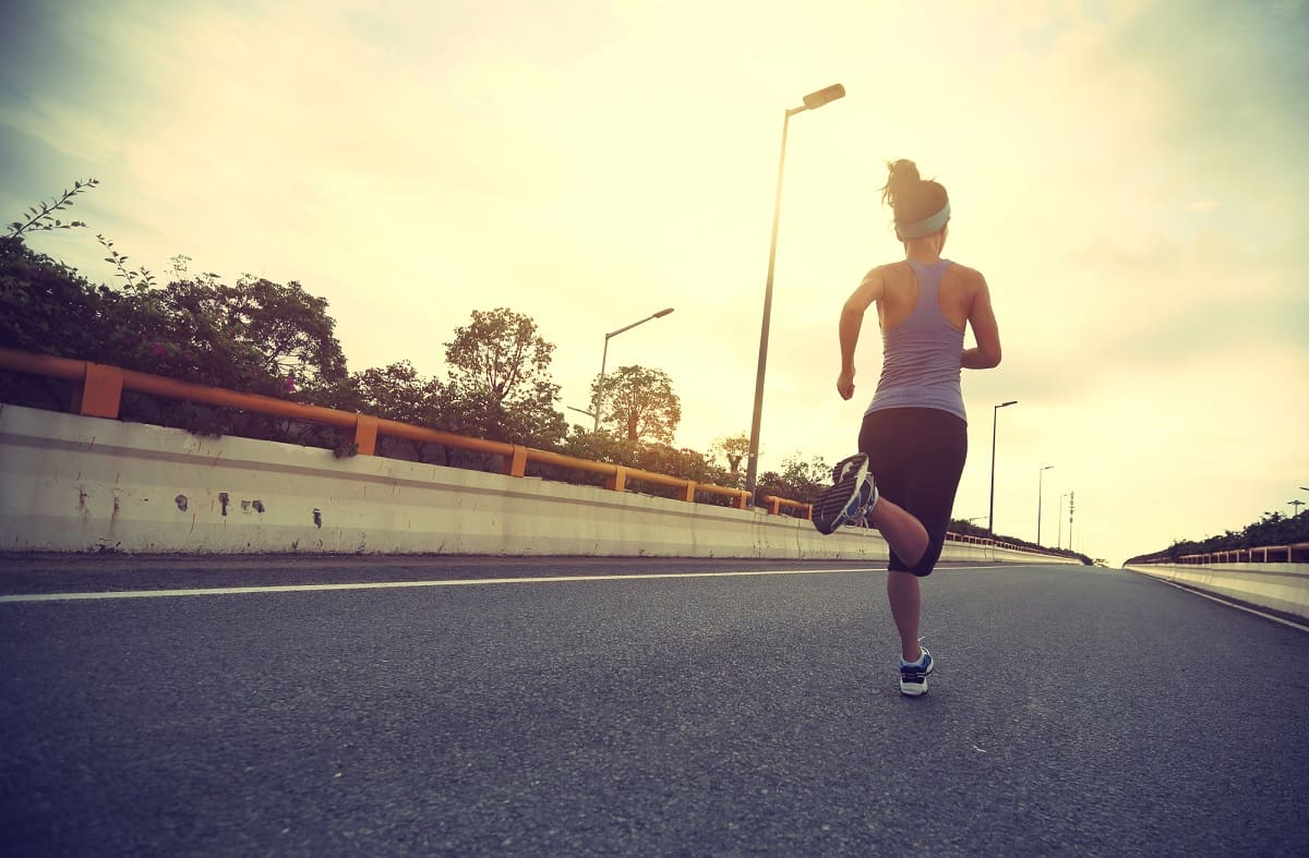 A female runner who is running on the street outside.