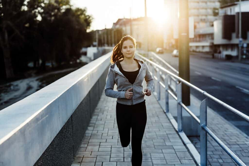 A woman running on the sidewalk, training for a 10K.