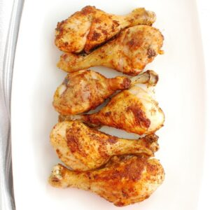 A white platter with six cooked air fryer chicken drumsticks.