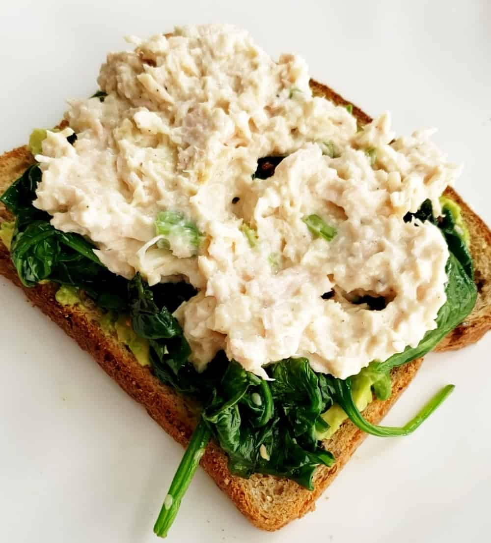 Avocado toast topped with spinach and tuna.
