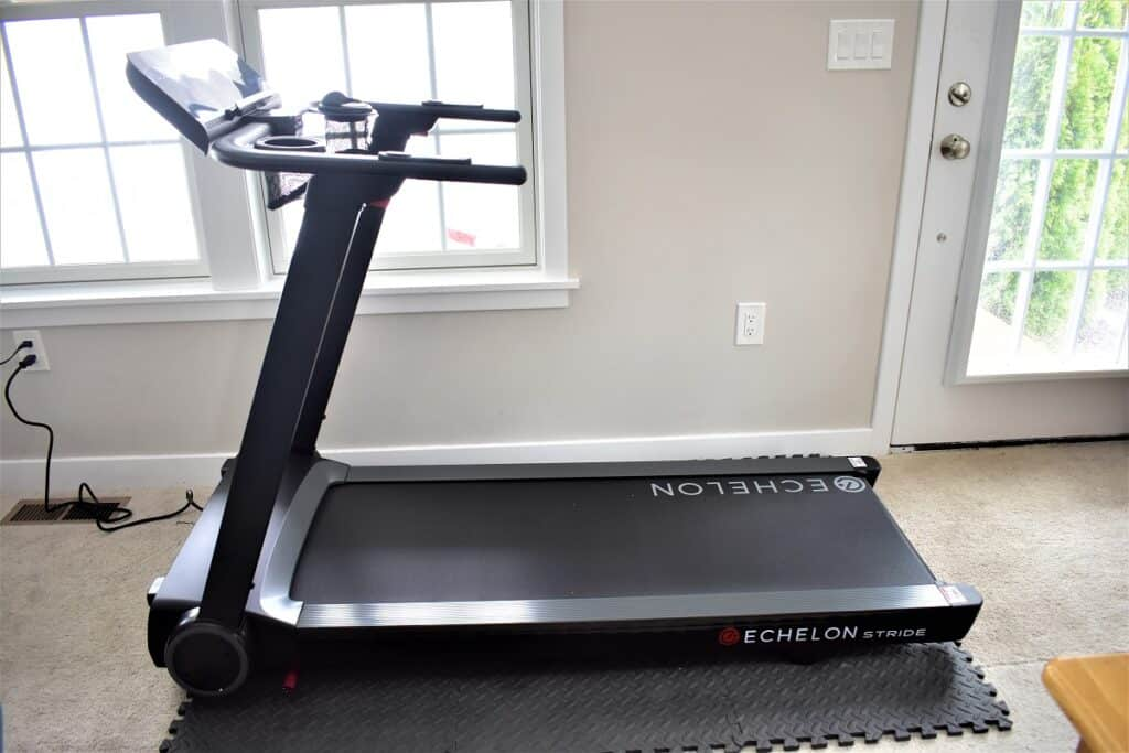 The Echelon Stride treadmill on a heavy duty foam mat, set up in a living room.