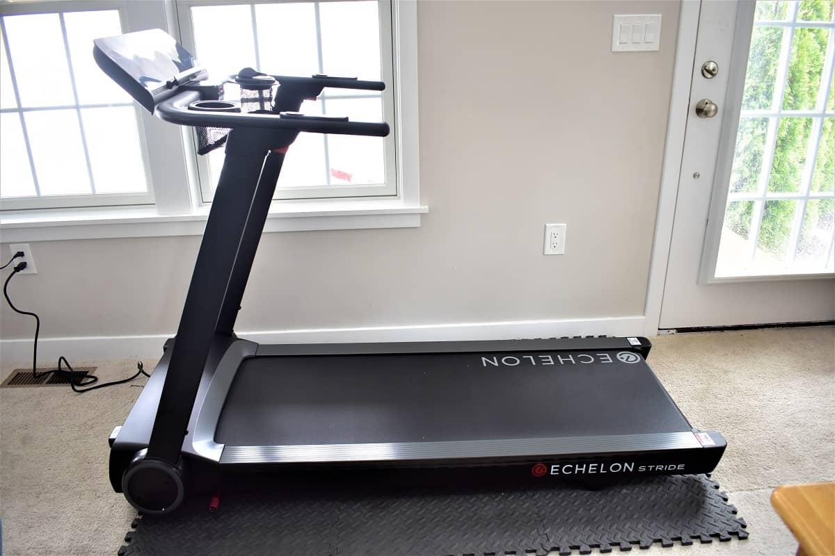 The Echelon Stride treadmill on a heavy duty foam mat, set up in a living room.