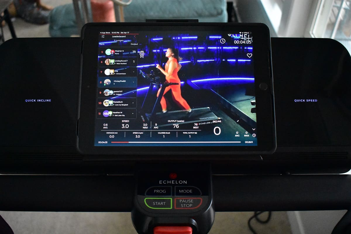 A tablet with a live running fitness class playing.