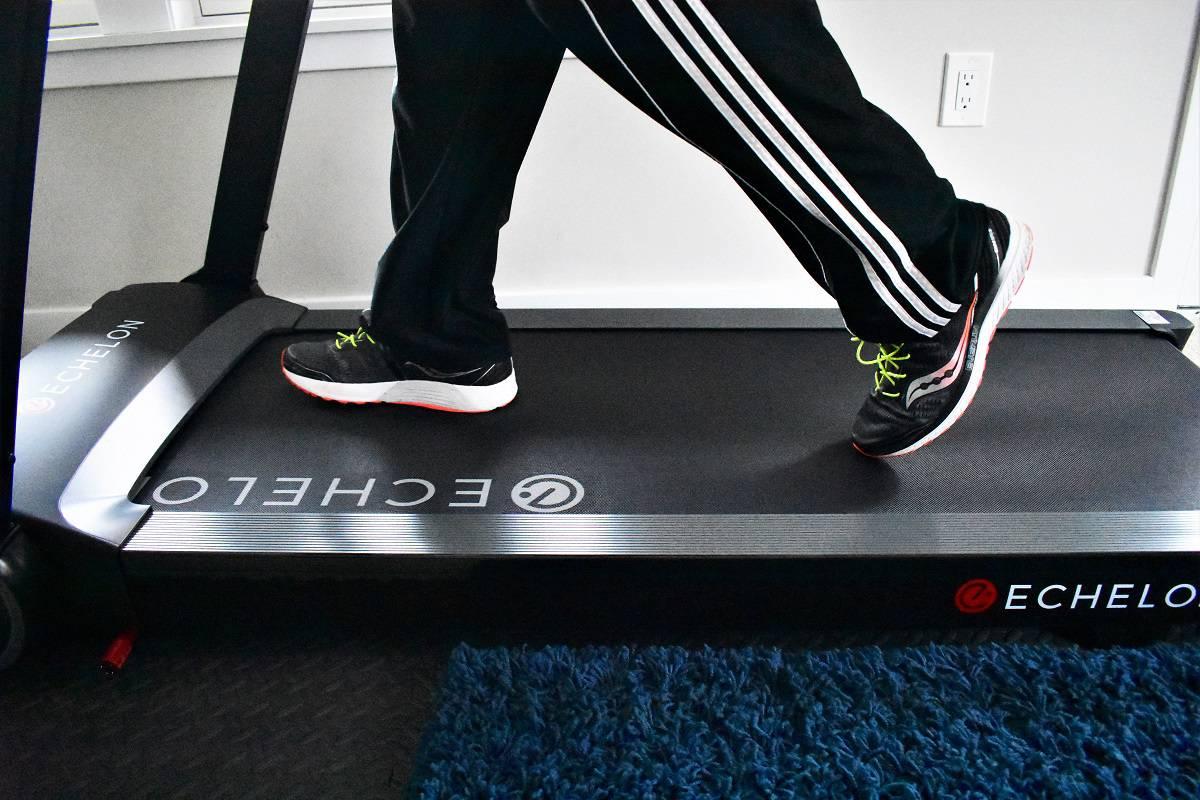 A mans feet walking on a treadmill.